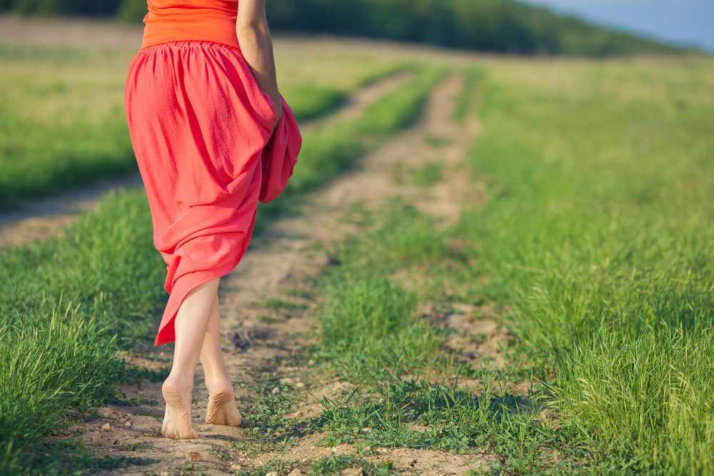 девушка в красной юбке идет босиком по тропинке