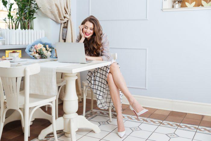 Девушка в клетчатой юбке сидит за столом перед компьютером