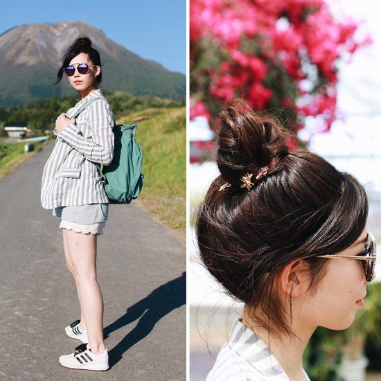 Девушка в полосатом пиджаке и в очках стоит на дороге