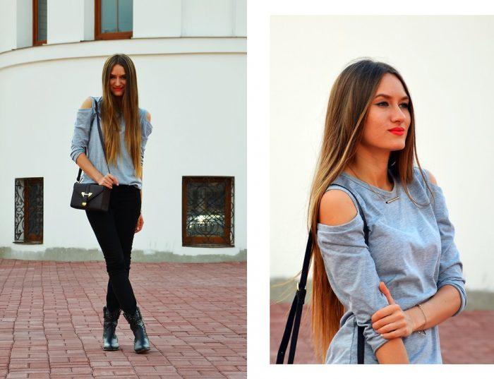 Девушка в черных брюках и серой кофте с открытыми плечами
