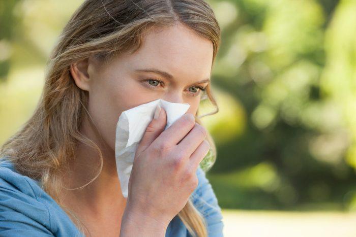 Девушка вытирает нос салфеткой