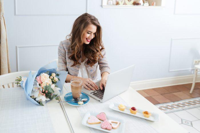 Девушка сидит за столос с цветами, кофе и пироженным м переписывается по компьютеру