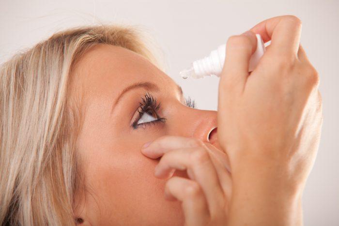 Девушка закапывает капли в глаза