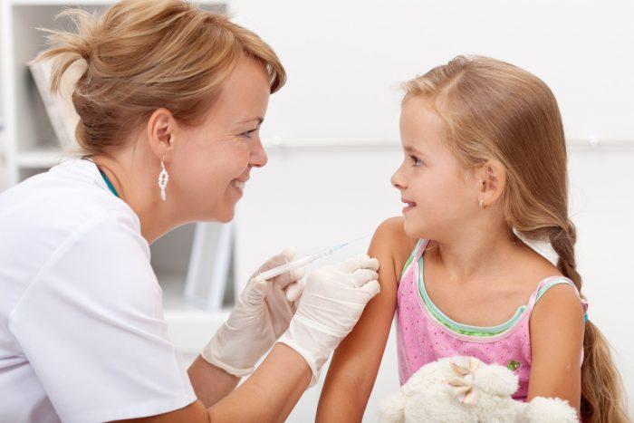 Доктор собирается сделать укол в плече девочке