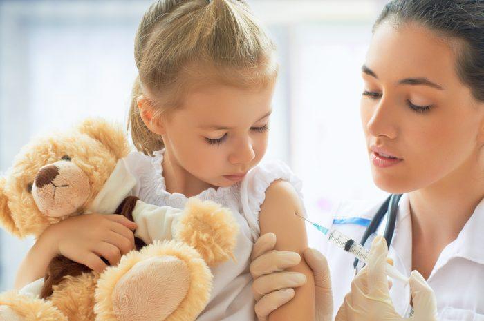 Доктор делает укол в плече девочке