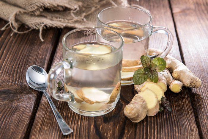 На деревянном столе ложка и две большие прозрачные чашки с корнем имбиря