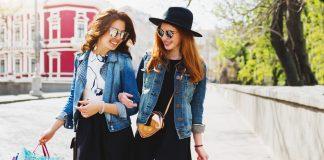 Две девушки в очках идут под руки с покупками