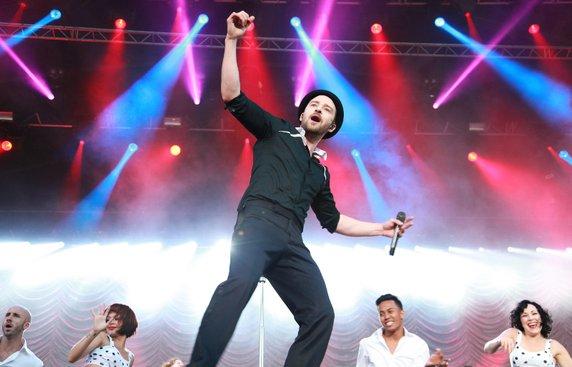 музыкант Джастин Тимберлейк на сцене в черной рубашке,брюках и шляпе