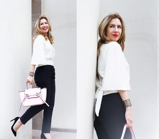 Девушка в черных брюках и белой кофте