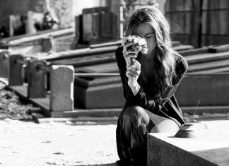 Девушка с цветами плачет у могилки