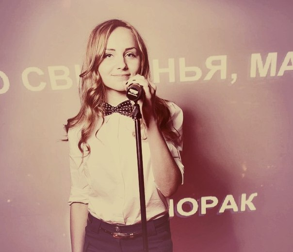 Суперфиналистка «Голос Країни — 6» Инна Ищенко в белой рубашке с бабочкой и с микрофоном
