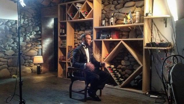 Иракли Макацария сидит на деревянном стуле в черном костюме