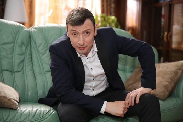 Кирилл Бин сидит на диване в костюме