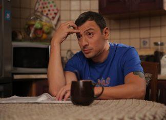 Кирилл Бин сидит за столом в синей футболке