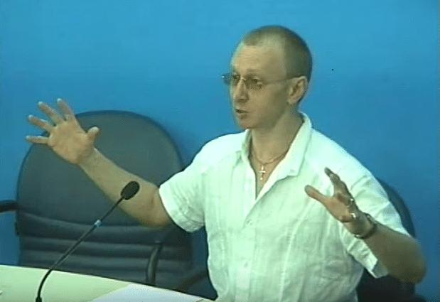 Константин Расин за трибуной в белой рубашке