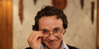 Константин Войтенко в рубашке,в пиджаке поправляет очки