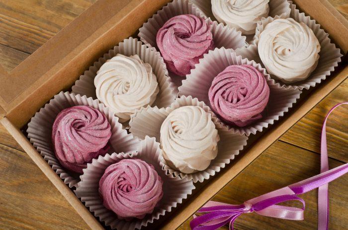 Зефир белый и розовый в коробке на деревянном столе