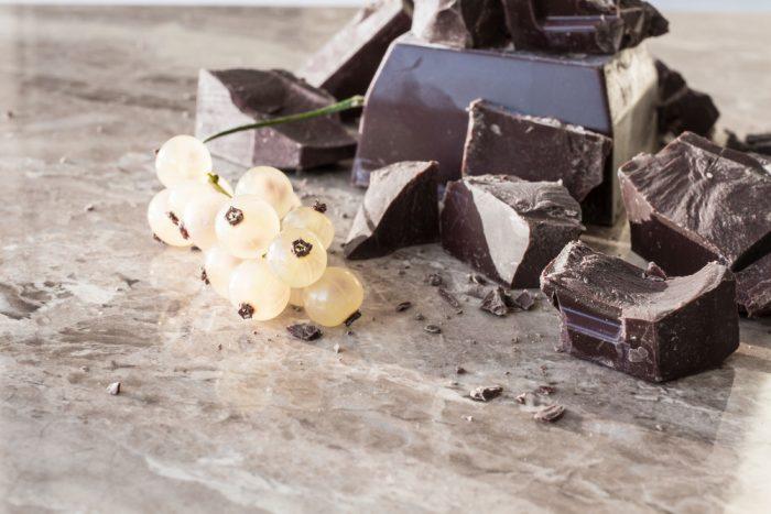Куски горького шоколада на столе с веточкой смородины