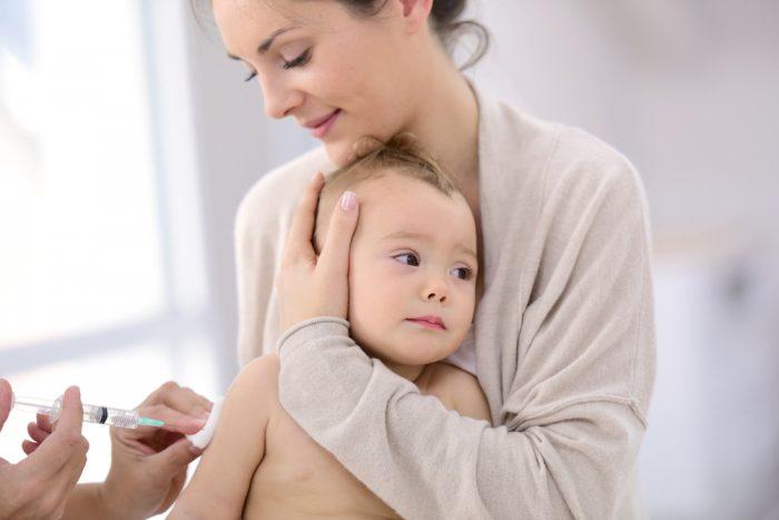 Мама держит ребенка, которому делают укол