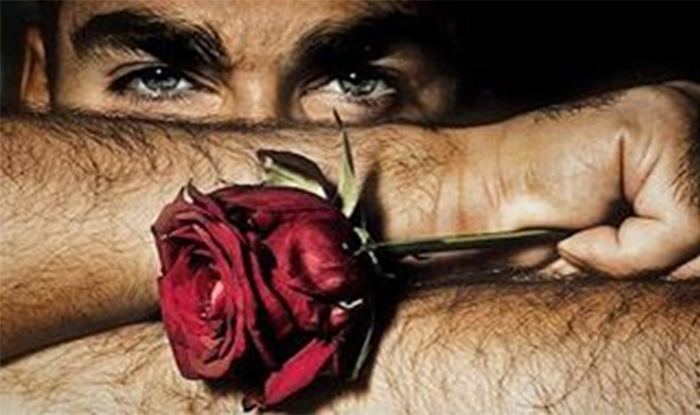 Мужчина держит красную розу