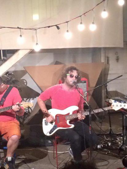 Ника Кочаров в розовой футболке играет на гитаре