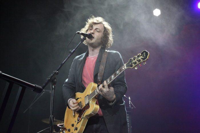 Ника Кочаров на сцене поет с гитарой