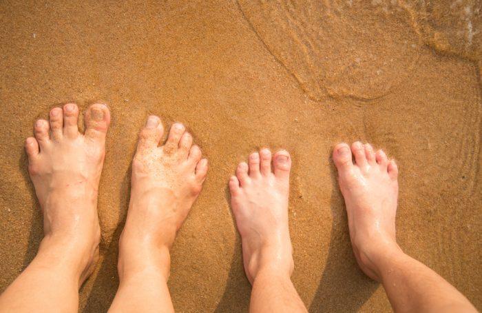 Ноги маленького мальчика и мужчины на песке пляжа