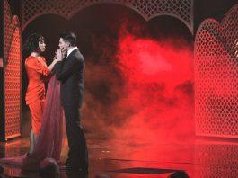 Злата Огневич в красном платье миди с мужчиной на сцене