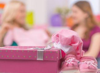 На переднем плане подарочная розовая коробка и детские вещи