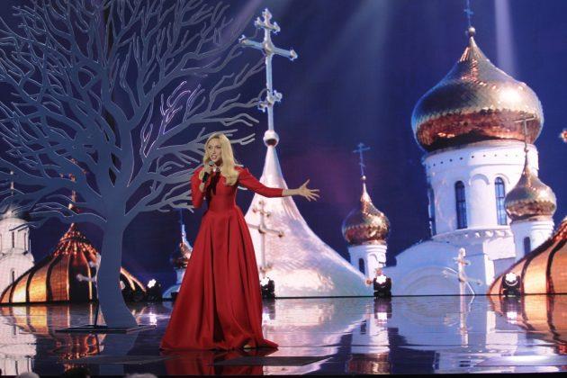 Ольга Полякова в красном закрытом макси-платье с белым воротничком на сцене