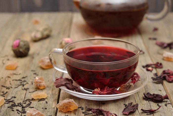 Прозрачная чашка с красным чаем,красными листьями и сухофпуктами