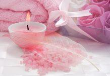 Розовая ароматическая свеча горит возле морской соли накрытой пером