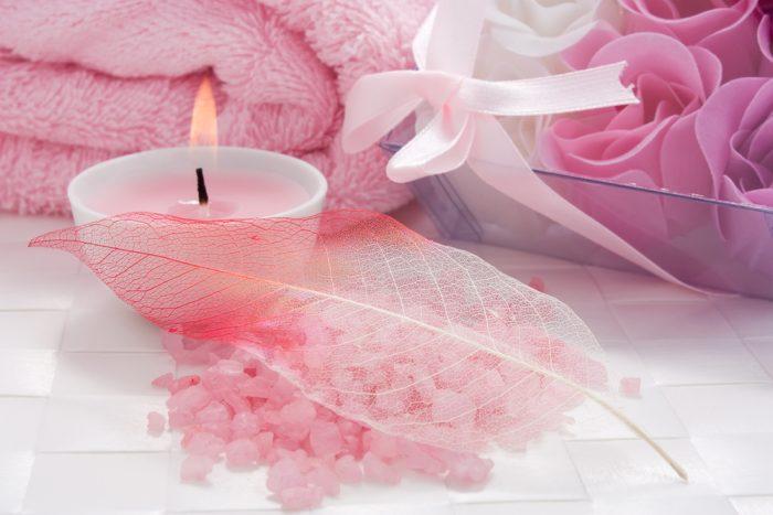 Розовая ароматическая свеча горит возле емкости с морской солью, накрытой пером