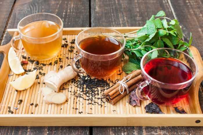 На деревянном подносе с орицейи мятой, три чашки чая:зеленый,черный и красный