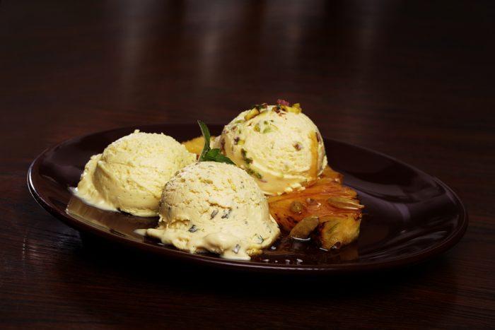 Три шарика ванильного мороженого с фисташками и карамелью