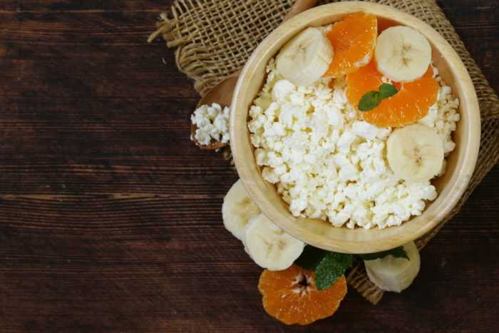 Творог в деревянной тарелке с колечками банана и апельсина