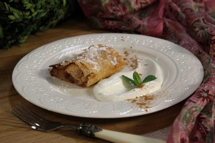 яблочный штрудель из лаваша на белой круглой тарелке