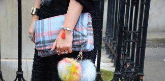 Женские руки держат клетчатый клатч с помпонами