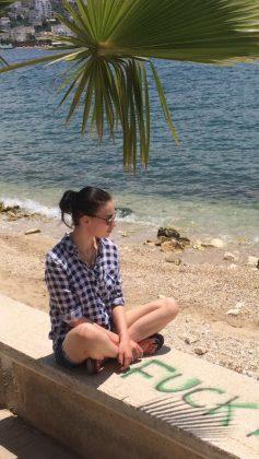Анастасия Приходько в клетчатой рубашке сидит у моря