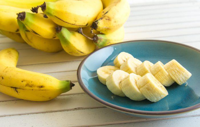 Бананы целые и порезанные на кружки на синей тарелке