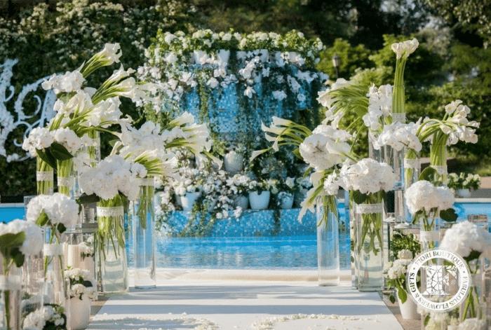 Белые цветы в стеклянных вазах возле фонтана
