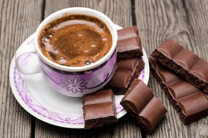 Чашка кофе возле кусочков шоколада на деревянной поверхности