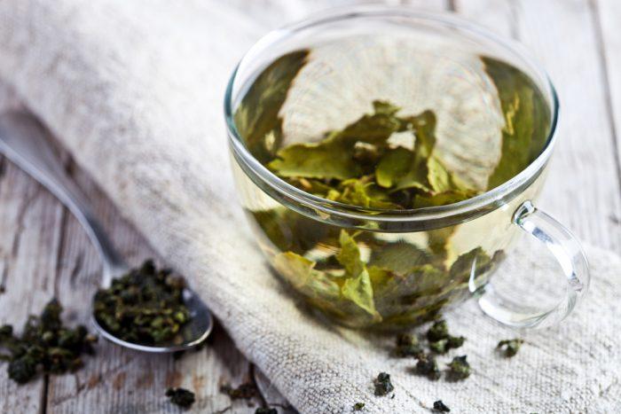 Чашка зеленого чая с листьями