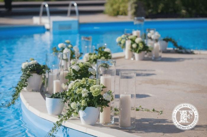 Цветы в белых горшках и белые свети у бассейна