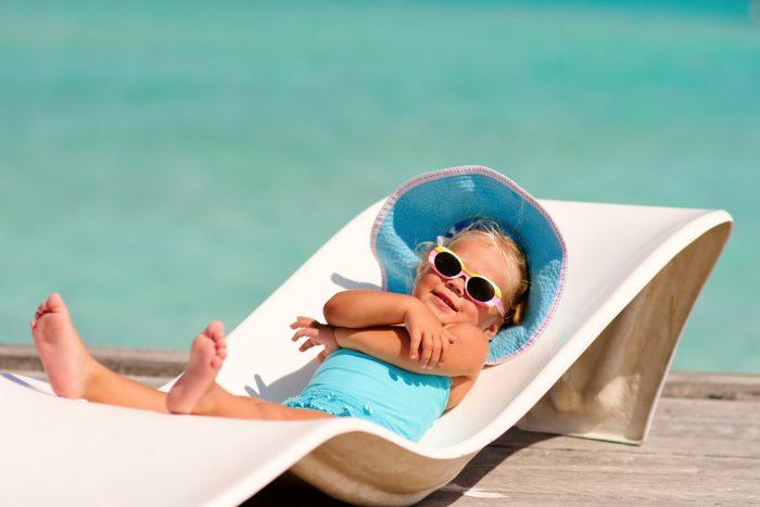 Девушка в голубой панаме лежит на лежаку у моря