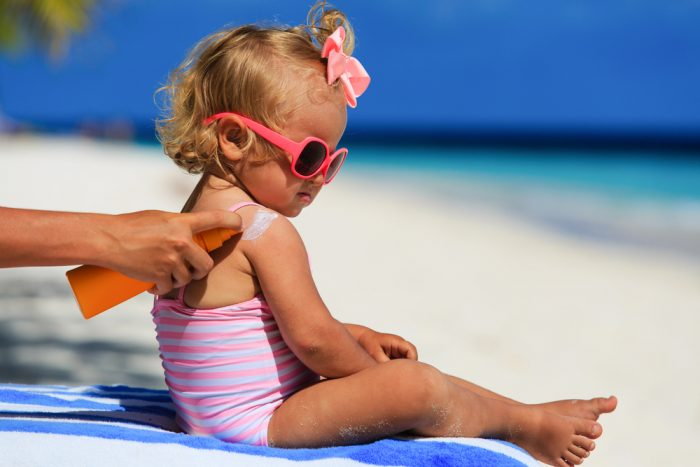 Девочке на пляже наносят крем на плечи