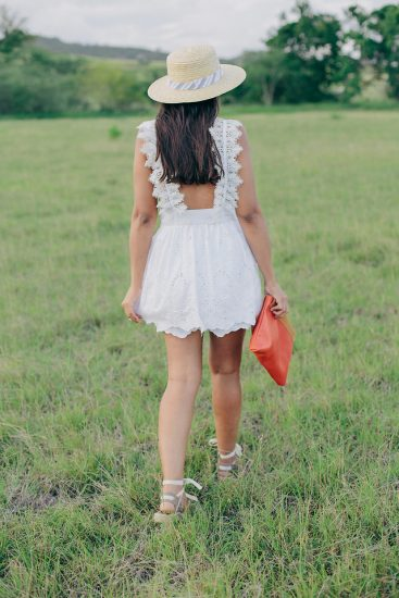 Девушка идет по траве в светлом сарафане и шляпе