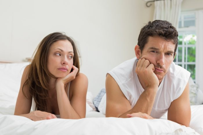 Девушка лежит возле мужчины и смотрит на него