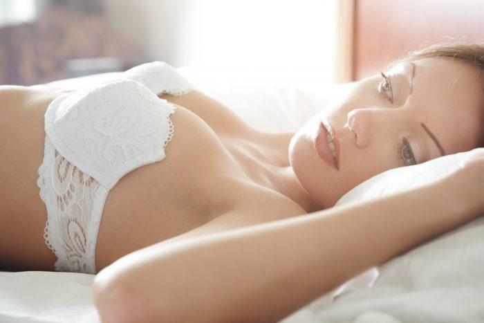 Девушка лежит на постеле в белом белье