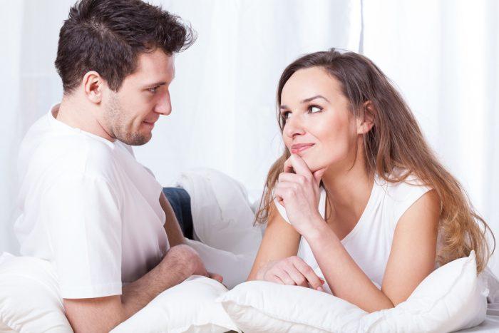 Девушка смотрит на парня лежа в постеле